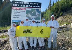 Amnesty International members outside of the Mount Polley disaster wearing hazmat suits